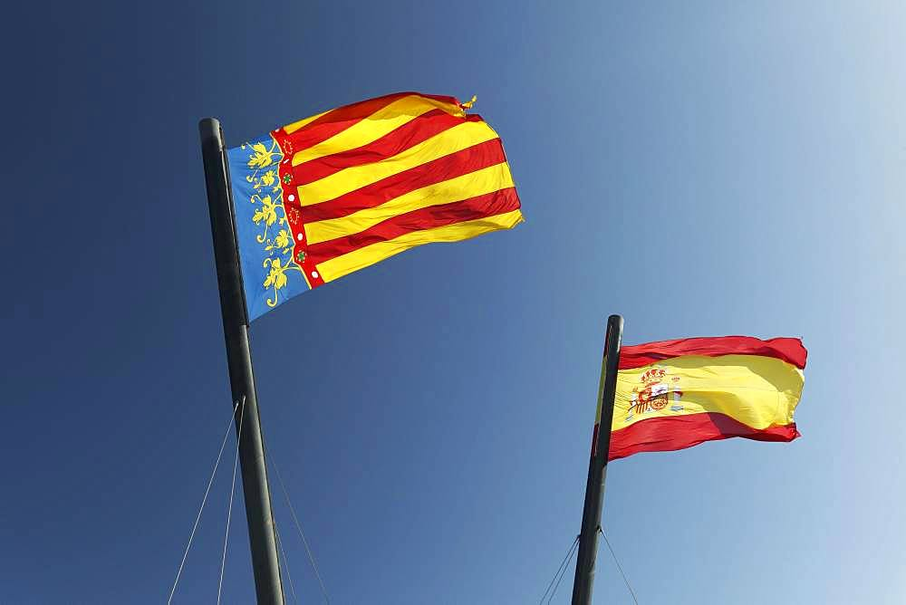 Two Spanish flags in the wind in front of blue sky, flag Valencia and flag Kingdom of Spain, Valencia, Spain, Europe
