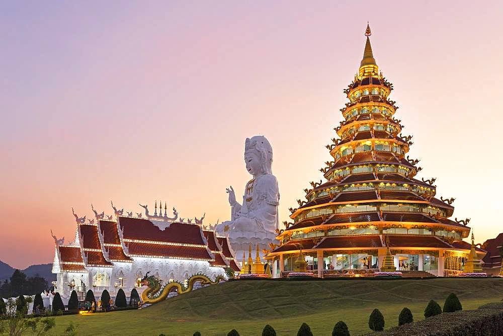 Nine-storey Chinese pagoda and chapel in front of huge Guan Yin statue at sunset, Wat Huay Pla Kang temple, Kuan Yin, Chiang Rai, Northern Thailand, Thailand, Asia
