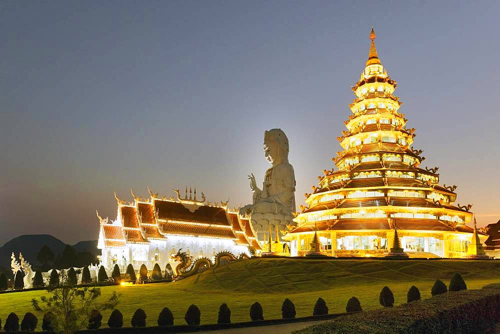 Nine-storey Chinese pagoda and chapel in front of the huge Guan Yin statue at dusk, Wat Huay Pla Kang temple, Kuan Yin, Chiang Rai, Northern Thailand, Thailand, Asia