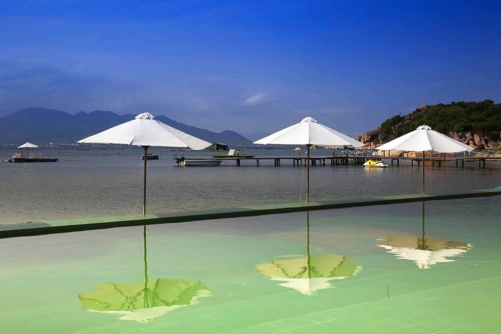 Swimming pool with parasols, Sao Bien holiday resort in the bay of Cam Ranh, South China Sea, Ninh Thuan, Vietnam, Asia