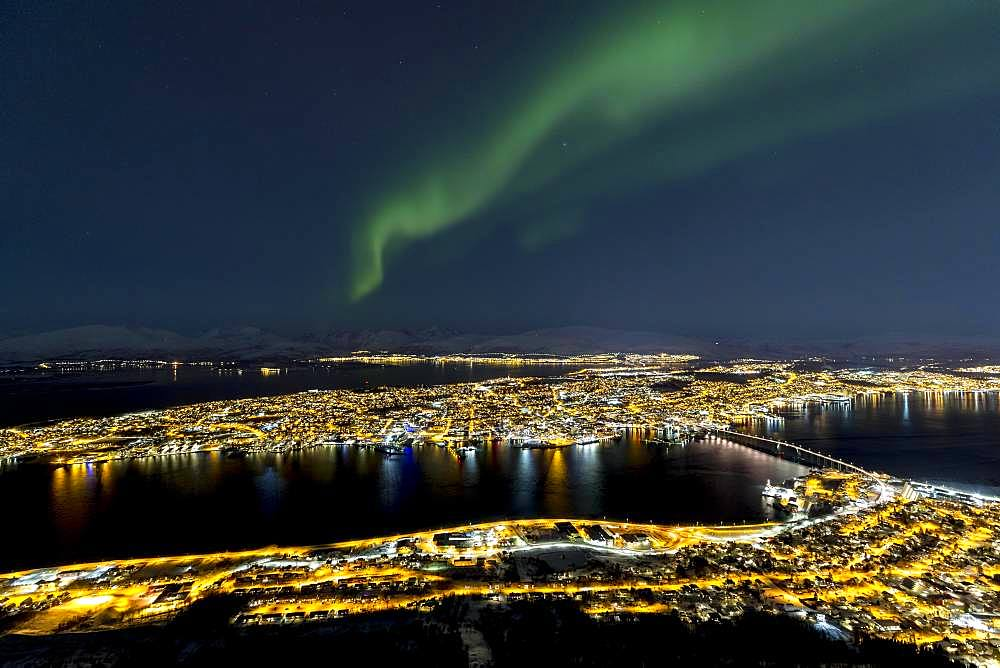 Illuminated city and aurora borealis above Fjellheisen, Tromsoe, Norway, Europe