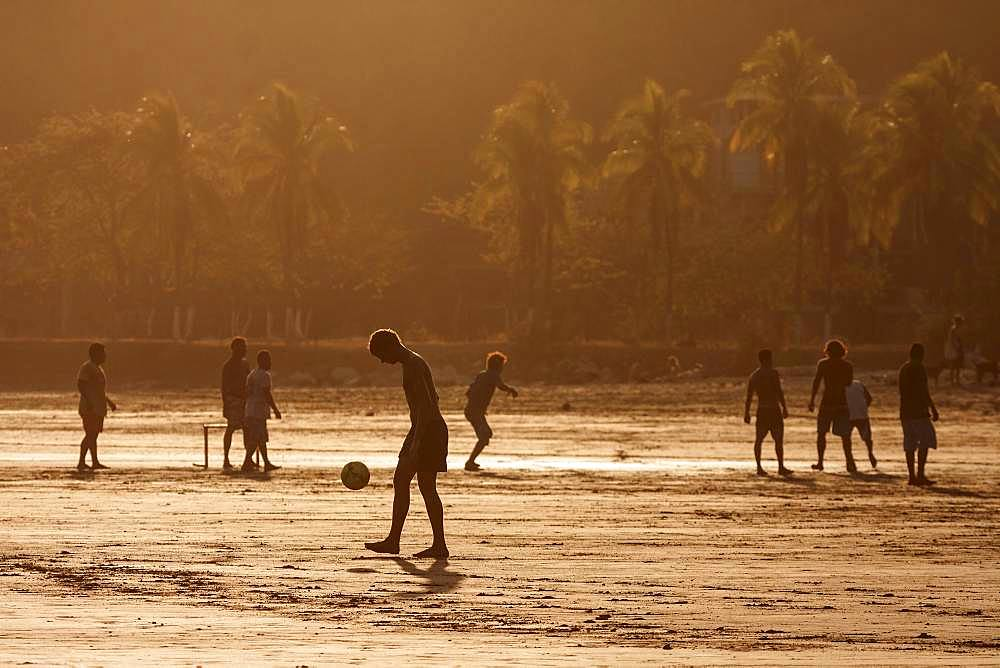 Young people playing football on the beach, evening light, Playa Samara, Samara, peninsula Nicoya, province Guanacaste, Costa Rica, Central America
