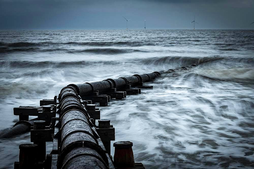 Corroded iron pipe, sewage pipe in the sea surf under a dark sky, Blyth, Northumberland, Great Britain