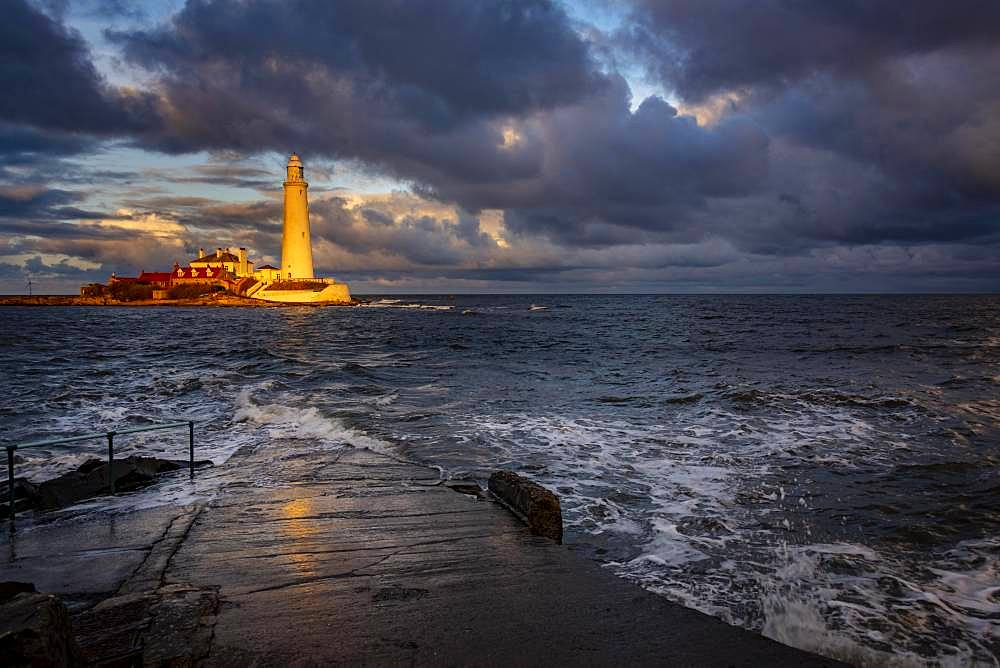 Lighthouse, St. Mary's Lighthouse with washed over road at high tide with dramatic clouds at sunset, Coast of Tyne, Northumberland, Great Britain