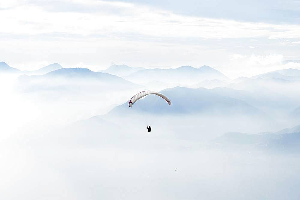 Paragliding over the mountains in clouds near Malcesine at Lake Garda, aerial view, Veneto, Italy, Europe