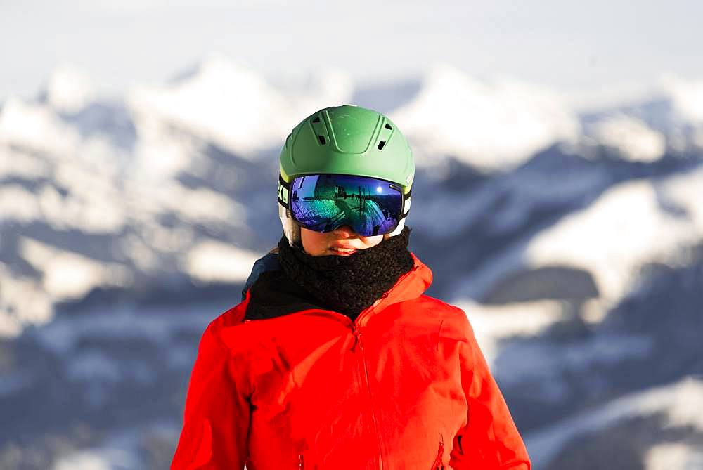 Female skier with ski helmet and ski goggles looks into the camera, portrait, back mountains, SkiWelt Wilder Kaiser, Brixen im Thale, Tyrol, Austria, Europe