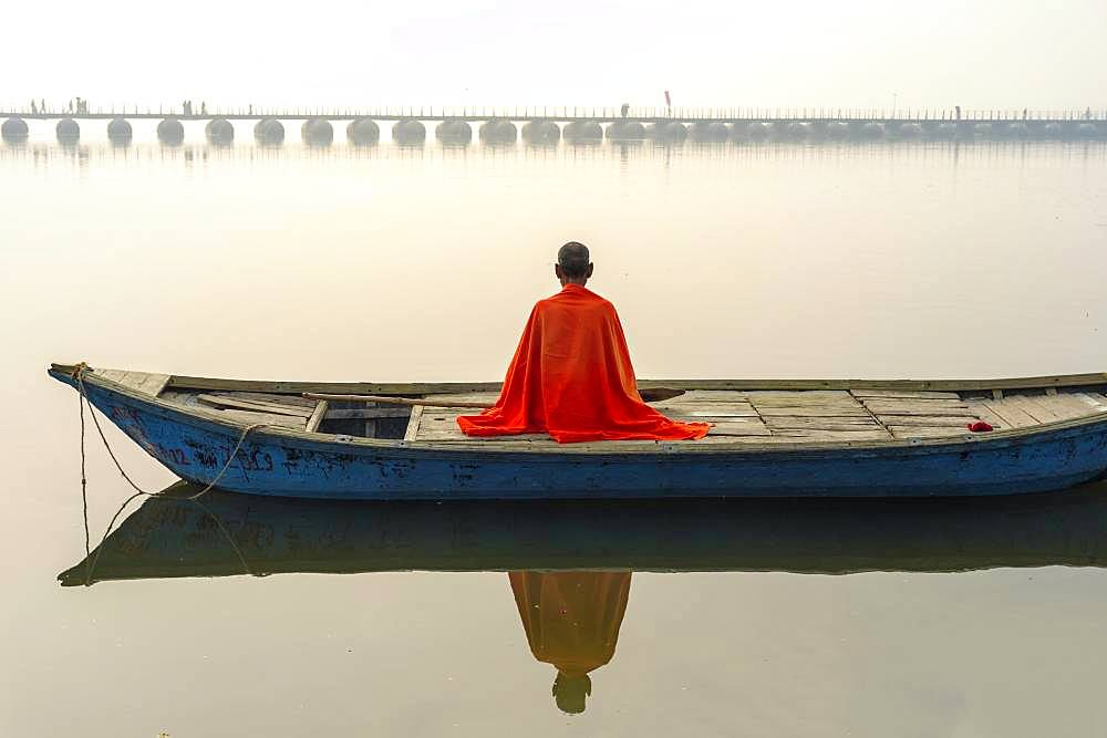Sadhu with red shawl on a boat on the Ganges river at sunrise, Allahabad Kumbh Mela, world's largest religious gathering, Uttar Pradesh, India, Asia