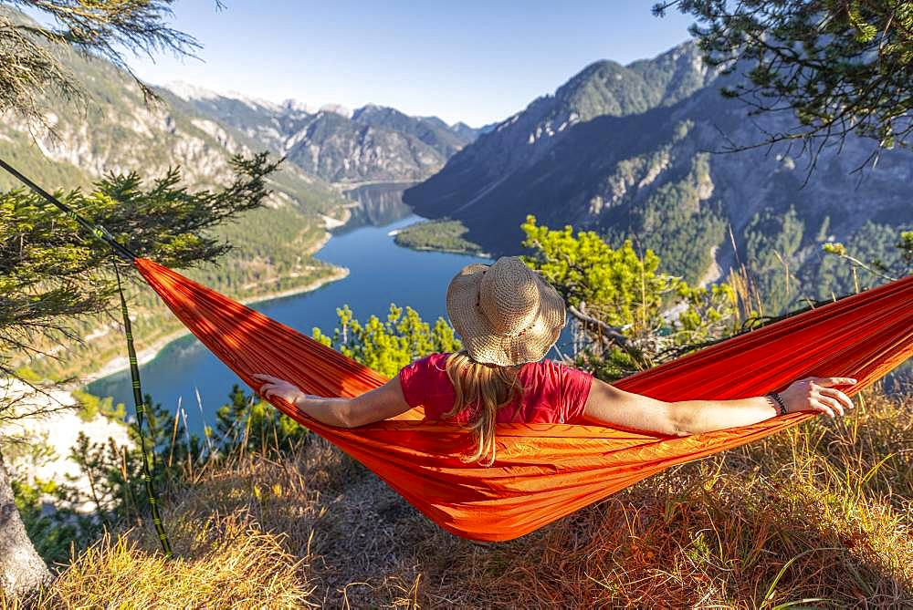 Woman with a sun hat sitting in an orange hammock, panoramic view of mountains with lake, Plansee, Tyrol, Austria, Europe - 832-385408