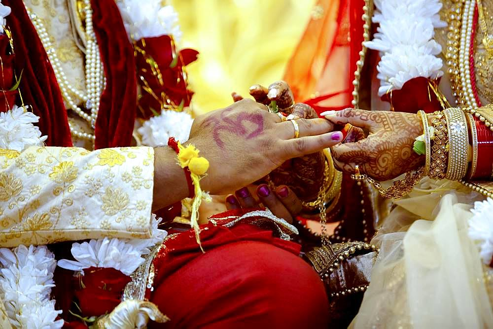 Bride with bridal jewelry and henna decoration on her hand attaches ring to the grooms finger at traditional religious ceremony at a Hindu wedding, Mauritius, Africa