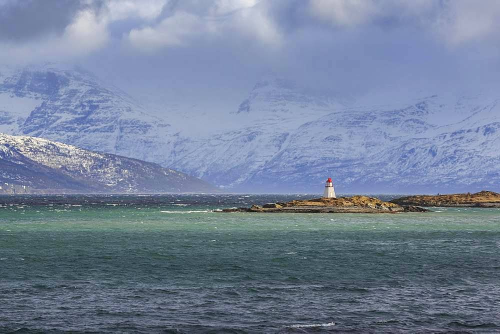 Lighthouse on the island Ytre Nortasholmen in front of snow covered mountains, Lyngenfjord, Troms, Norway, Europe