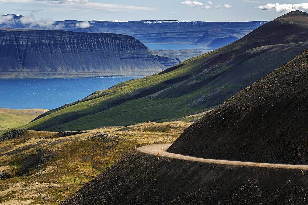 Gravel road meanders through volcanic landscape, near Hrafnseyri, Westfjords, Iceland, Europe