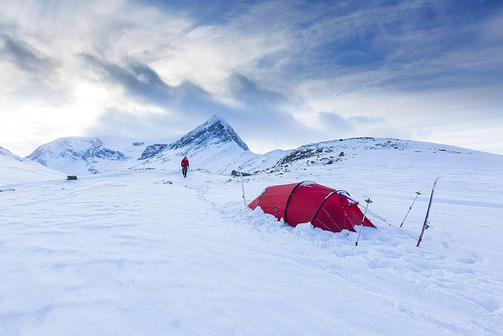 Red tent in the snow, on the long-distance hiking trail Kungsleden, Province of Lapland, Sweden, Europe