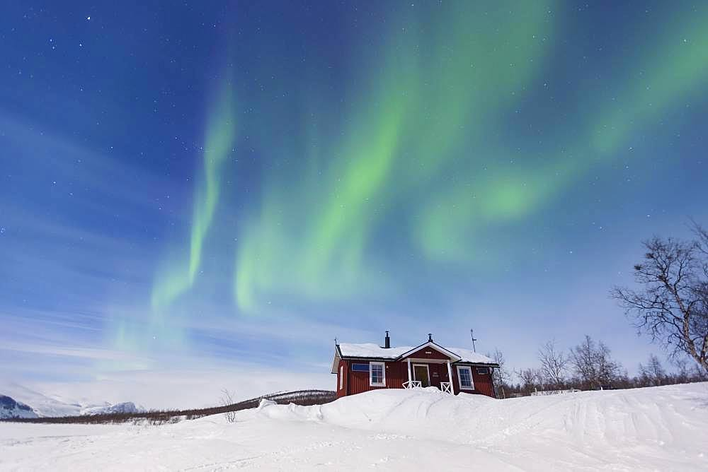 Northern Lights (Aurora borealis) above a Swedish red house in winter, Kungsleden, Province of Lapland, Sweden, Europe
