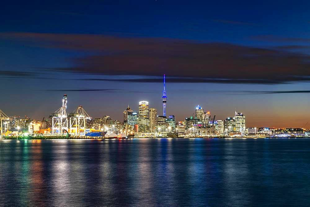 Illuminated skyline of Auckland at sunset, Waitemata Harbour, Sky Tower, Central Business District, Auckland, North Island, New Zealand, Oceania