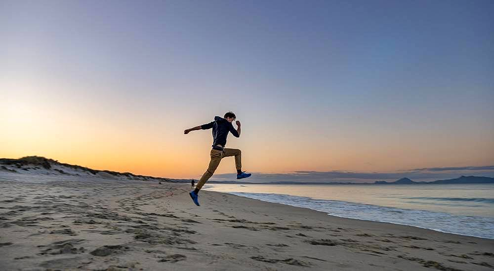 Young man jumps into the air, beach Waipu Beach at sunset, Waipu Cove, Northland, New Zealand, Oceania