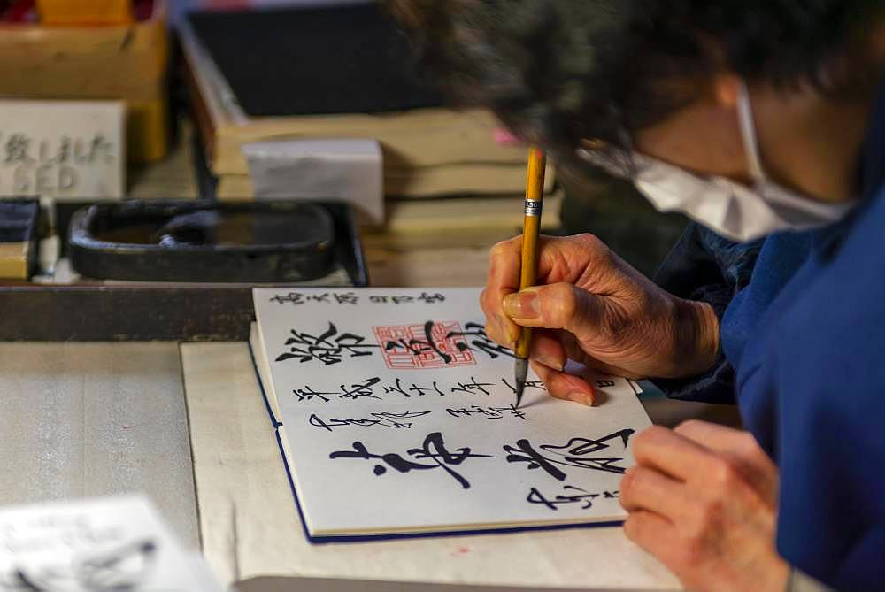 Woman writes Japanese characters, calligraphy, lucky charms to buy in Todaiji Temple, Japan, Nara, Japan, Asia