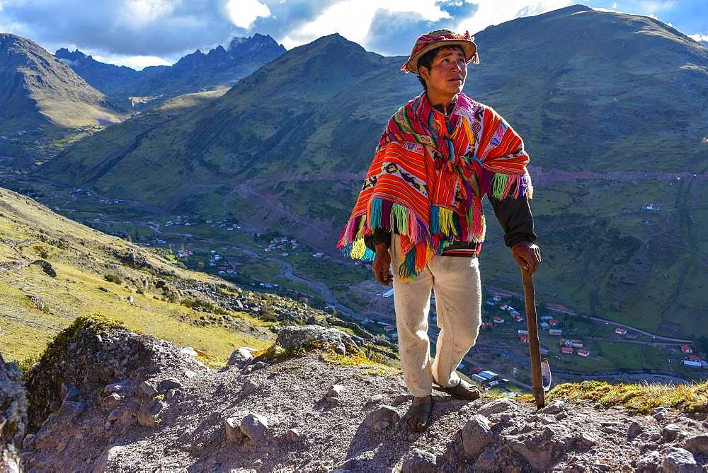 Indio mountain guide with hat and poncho in the Andes, near Cusco, Peru, South America