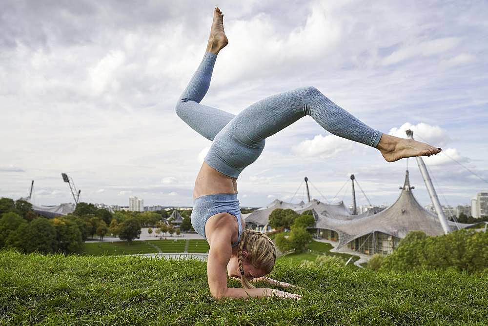 Young woman doing yoga, gymnastics, Olympiapark, Munich, Germany, Europe