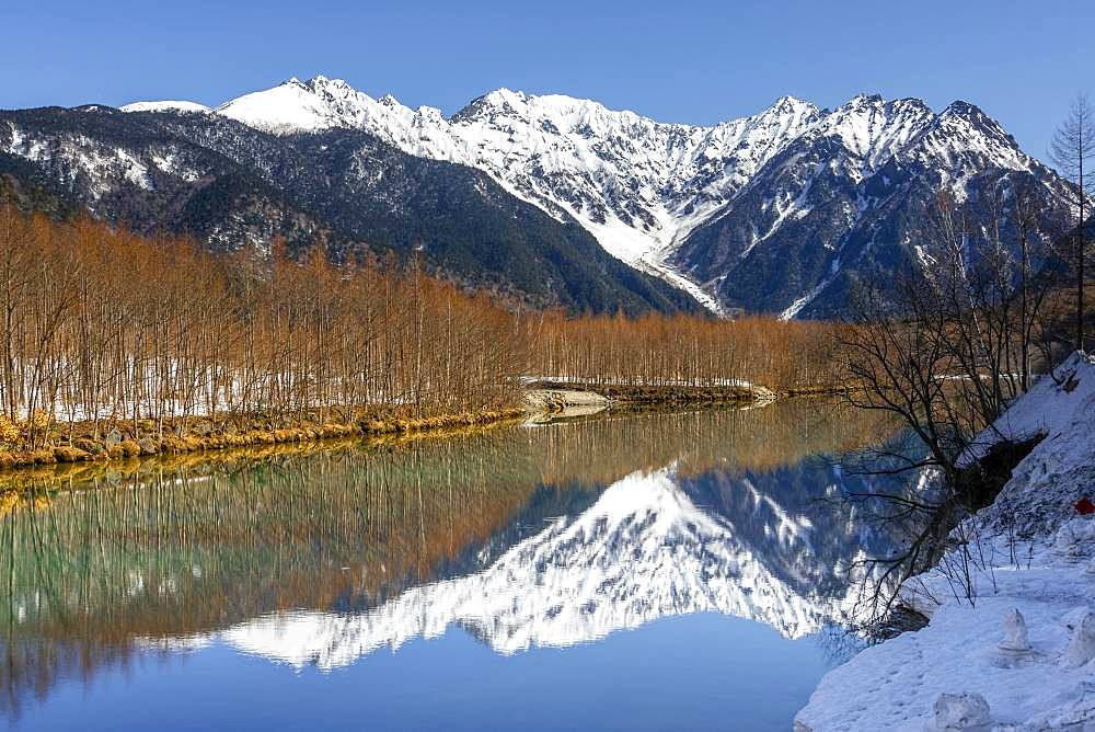 Snow-covered mountains at a lake, Japanese Alps reflected in Taisho Pond, snow-covered Mount Hotaka at the back, Kamikochi, Matsumoto, Nagano, Japan, Asia