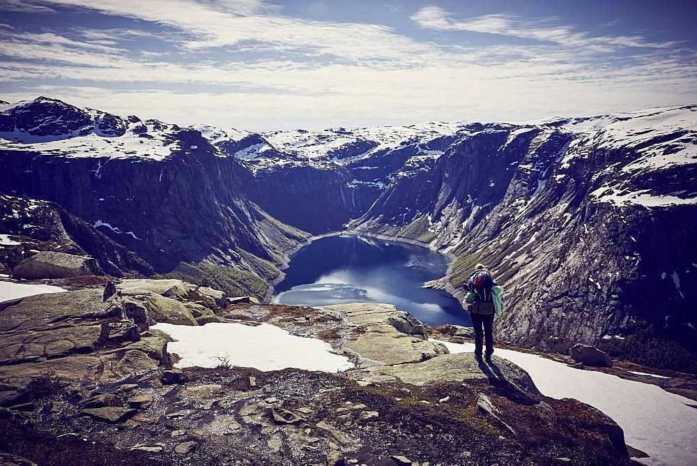 Young woman climbing to Trolltunga, view into the fjord, Sorfjord, near Odda, Norway, Europe
