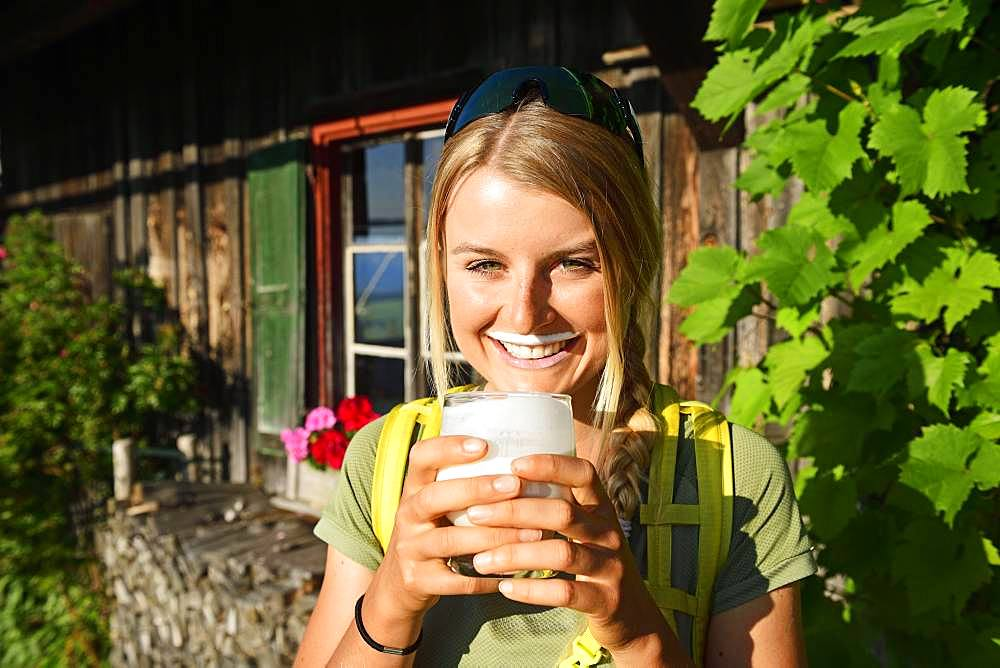 Young female hiker drinks buttermilk at the Kraftalm, Hohe Salve, Itter, Kitzbuehel Alps, Tyrol, Austria, Europe