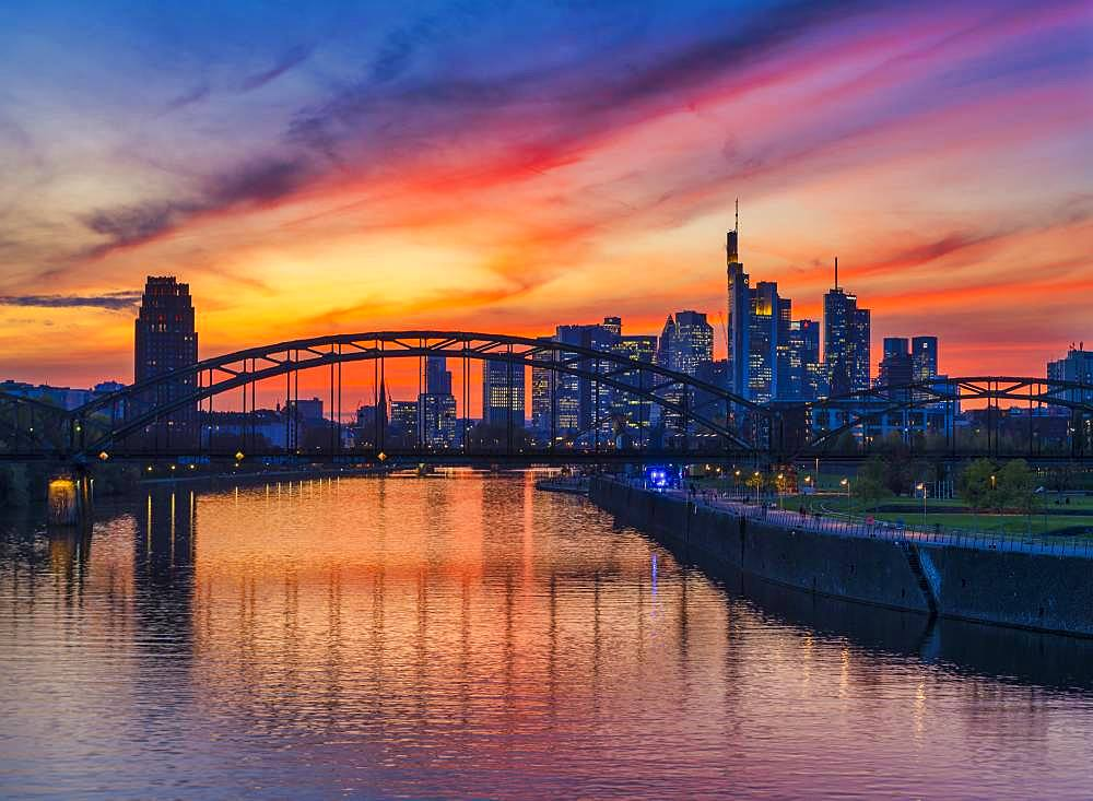 Skyline of Frankfurt in front of sunset with illuminated skyscrapers and reflections in the Main, Frankfurt am Main, Hesse, Germany, Europe