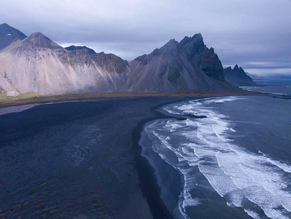 Aerial view, black lava edge with sea surf with mountain Vestrahorn, Cape Stokksnes, bay Hornvik, southeast Iceland, Iceland, Europe