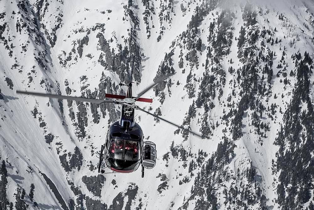Helicopter in front of snow-covered rock face, Himalaya, Gulmarg, Kashmir, India, Asia