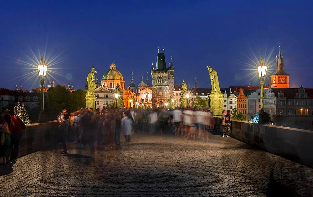 Karluv most, people on the Charles Bridge at dusk, in the back dome of the church Kreuzherrenkirche with old town bridge tower, Prague, Bohemia, Czech Republic, Europe