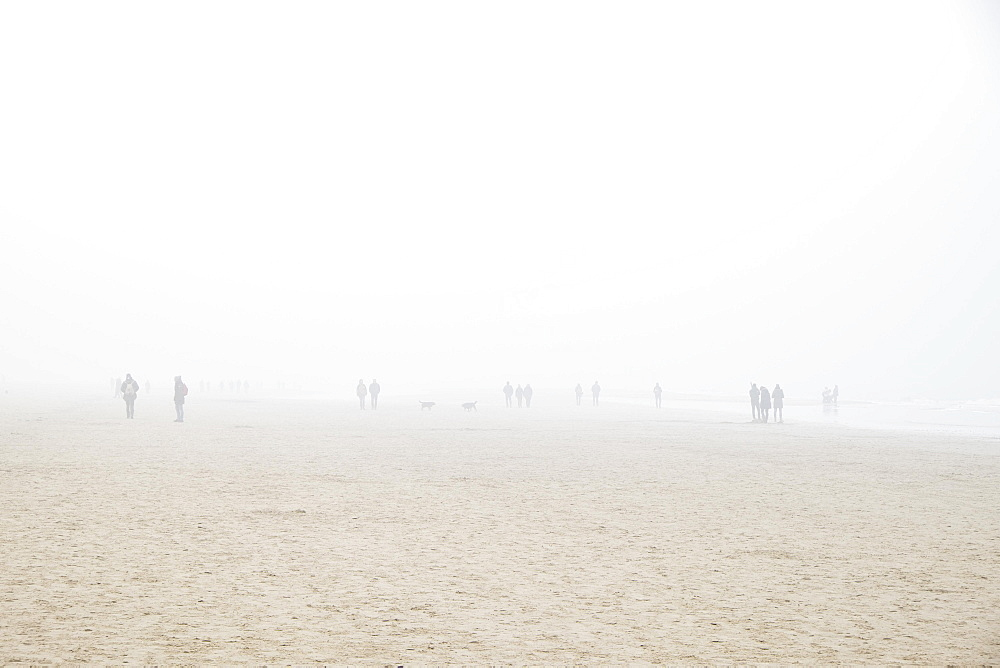 Beach with people in fog, Egmond aan Zee, Netherlands
