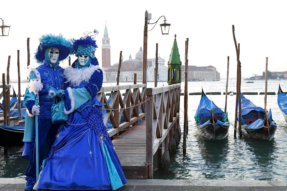 Blue couple standing in front of gondolas, carnival in Venice, church San Giorgio Maggiore in the back, Venice, Italy, Europe