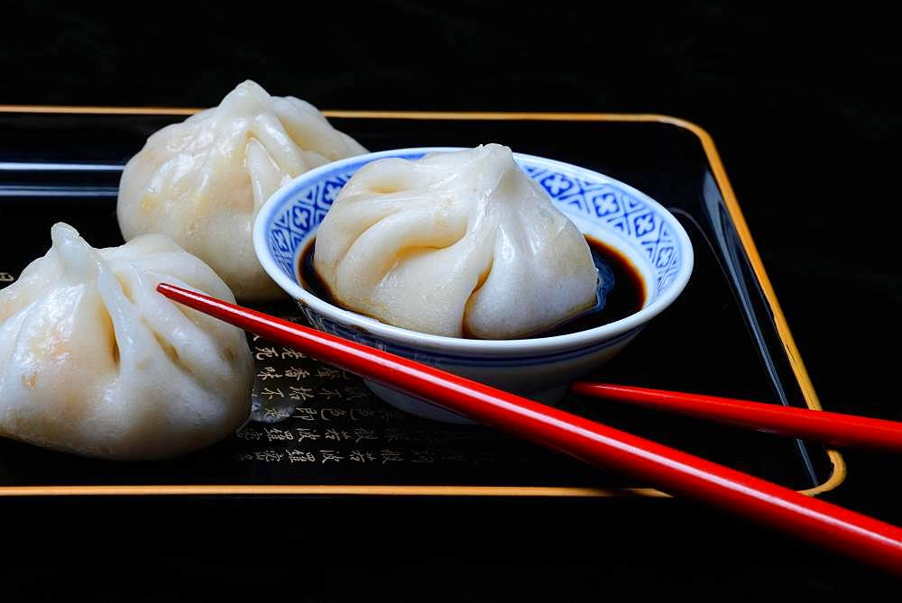 Dim Sum in Chinese bowl with soy sauce, filled dumplings, red chopsticks, Germany, Europe