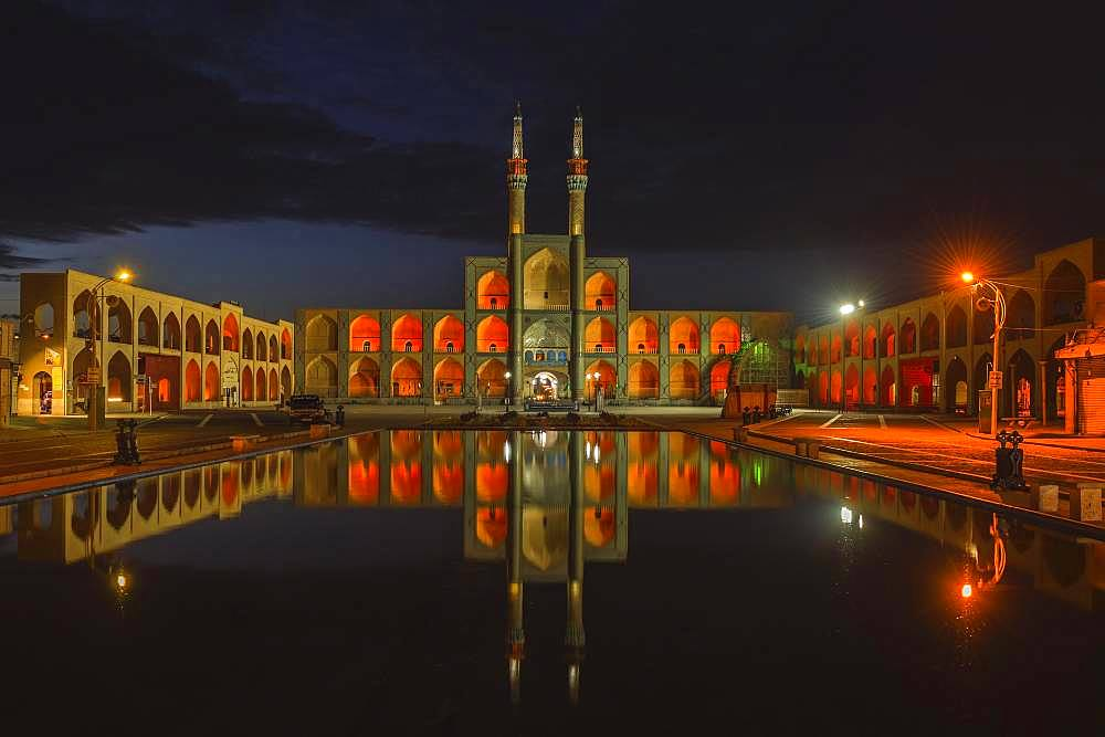 Amir Chaqmaq complex facade illuminated at sunrise and reflecting in a pond, Yzad, Yazd province, Iran, Asia