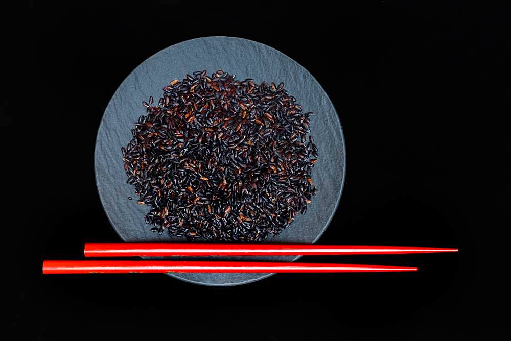 Black rice in bowl with red chopsticks, Germany, Europe