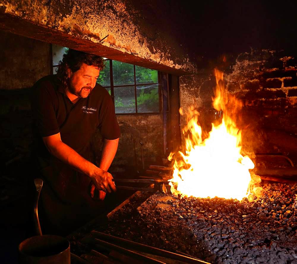 Blacksmith at the blacksmith's hearth, hammer mill Burghausen, Upper Bavaria, Bavaria, Germany, Europe