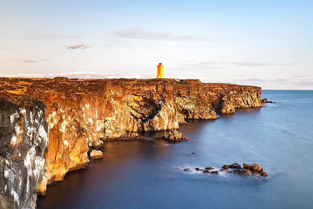 Orange lighthouse of Oendverdarnes stands at cliff coast, rocky coast of lava rock, long time exposure, Oendveroarnes, Snaefellsjoekull National Park, Snaefellsnes Peninsula, Snaefellsnes, Vesturland, Iceland, Europe