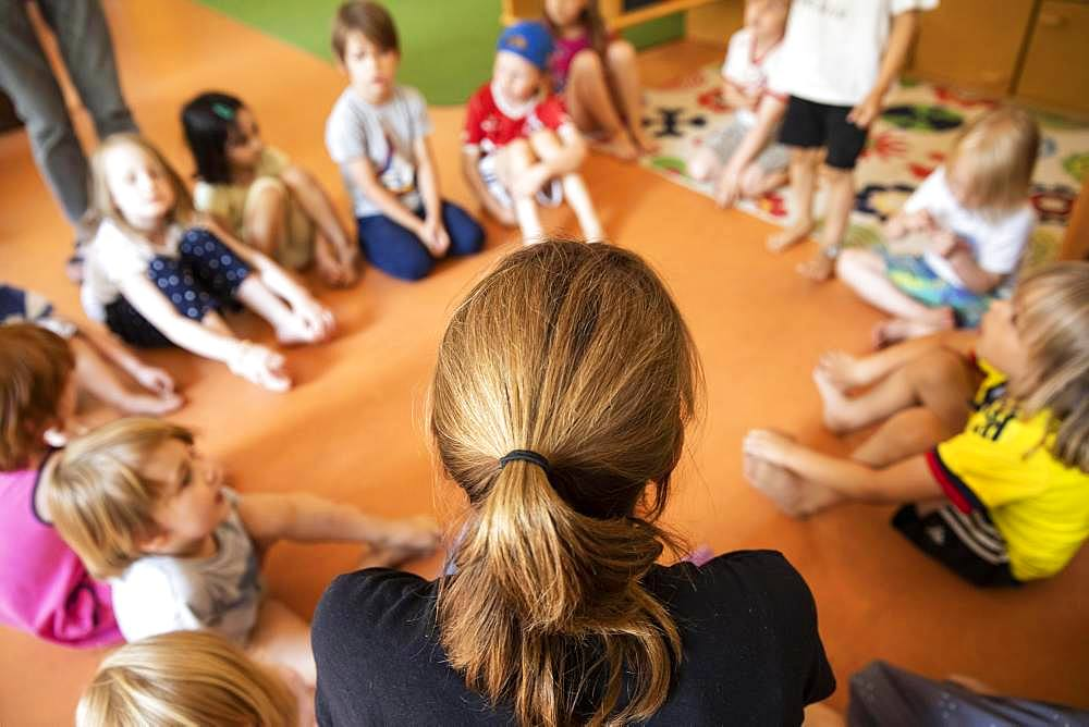 Educator sits with children in the kindergarten in a circle on the floor, Cologne, North Rhine-Westphalia, Germany, Europe
