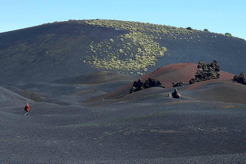 Wandering woman in volcanic lunar landscape, Reserva La Payunia, Province of Mendoza, Argentina, South America
