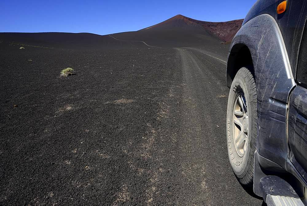 All-terrain vehicle on the road through volcanic lunar landscape, Reserva La Payunia, Mendoza Province, Argentina, South America