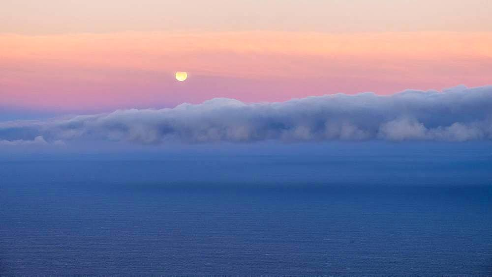 Moonset, sunrise mood at the sea, clouds in the sky, Spain, Europe