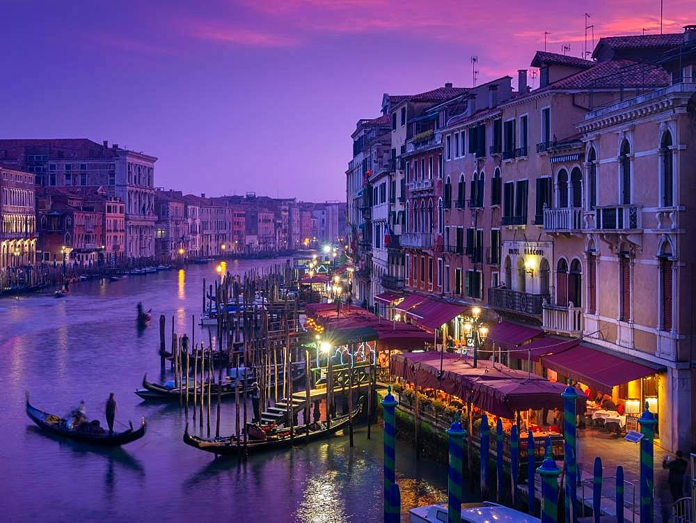 View from the Rialto Bridge on the Canal Grande with gondolier at sunset, Venice, Italy, Europe