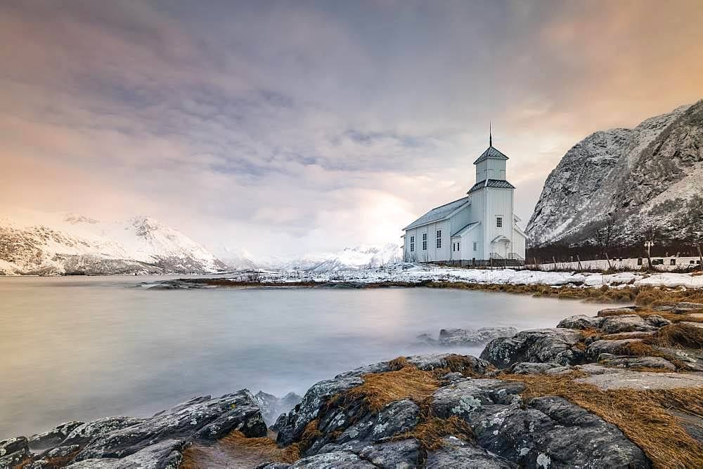 Church of Gimsoy in front of snowy mountains, Gimsoykirke, Gimsoy, Lofoten, Norway, Europe