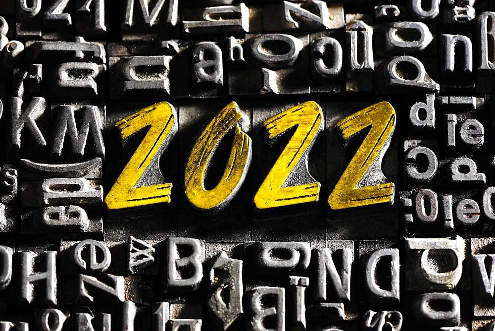 Old lead letters with golden writing show the word 2022, Germany, Europe