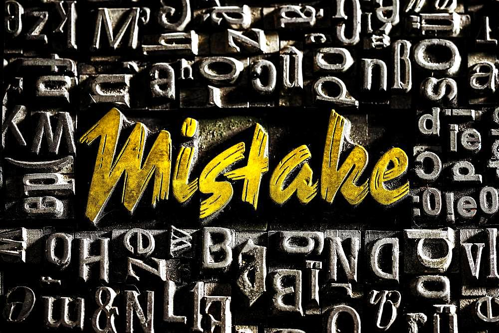 Old lead letters with golden writing show the word Mistake, Germany, Europe