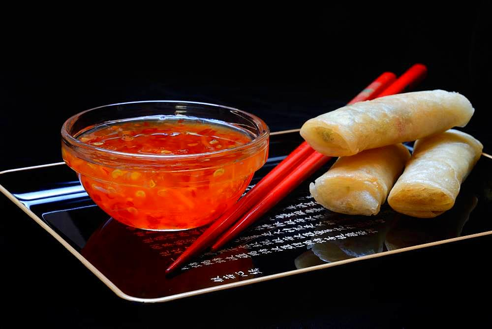Chilli sauce in glass bowl, spring rolls and chopsticks, Germany, Europe