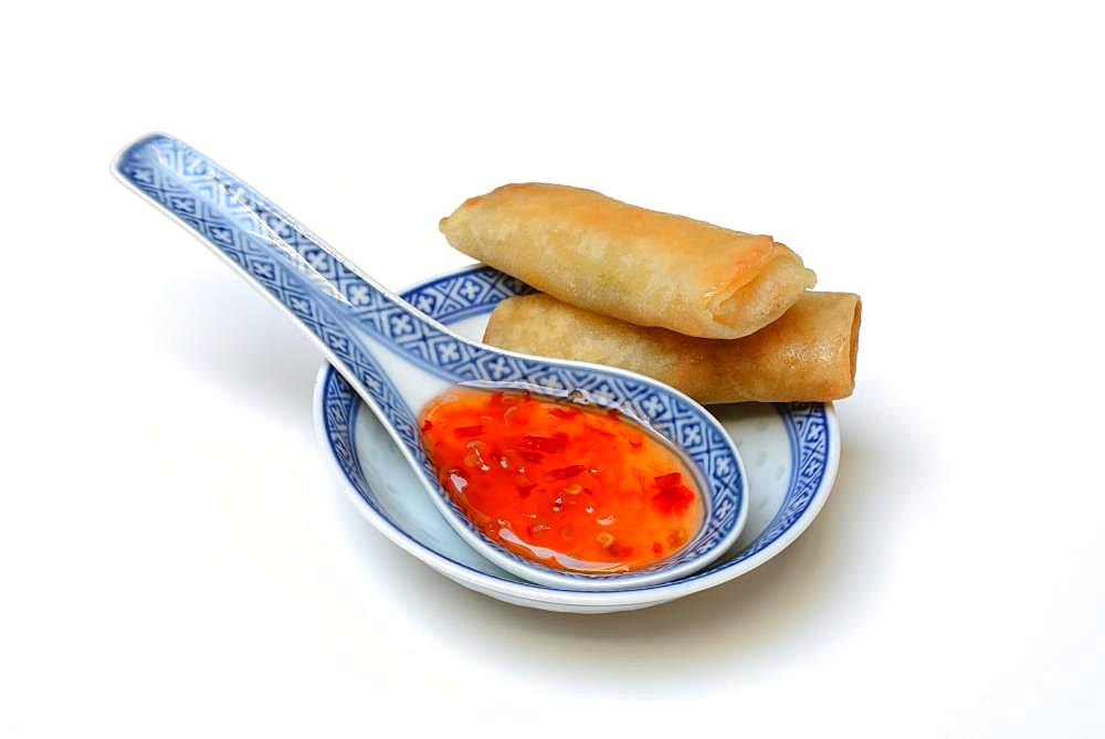 Chilli sauce in Asian spoon and mini spring rolls, Germany, Europe