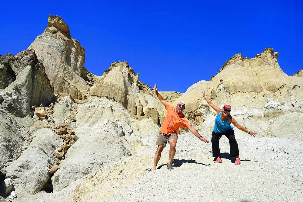 Two tourists at the bizarre rock formations of Cerro Alcazar, Calingasta, San Juan Province, Argentina, South America