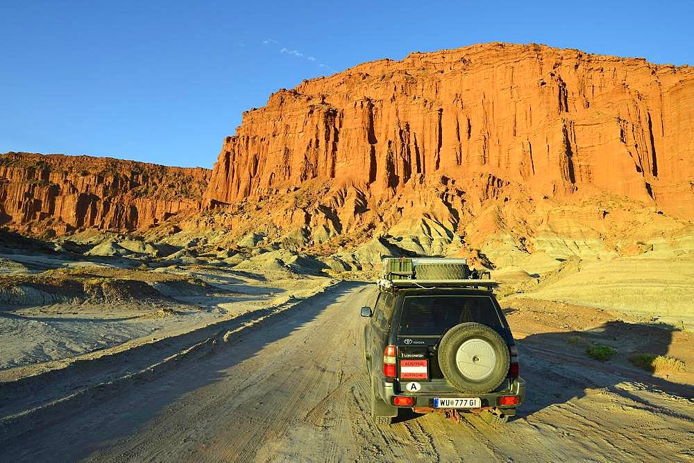 Off-road vehicle, Toyota Land Cruiser on the road in front of a red rock face, Ischigualasto Nature Reserve, San Juan Province, Argentina, South America