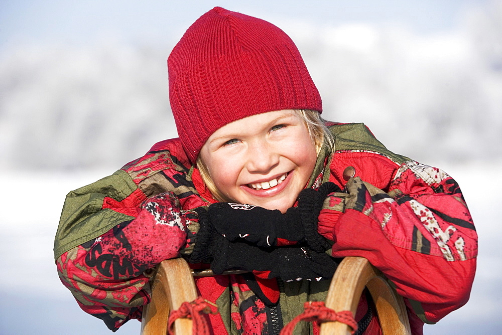Little girl leaning on a sledge and laughing, portrait, Upper Austria, Austria, Europe