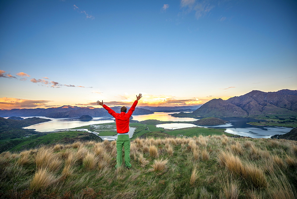 Hiker stretches his arms in the air, panoramic view of Wanaka Lake and mountains at sunset, Rocky Peak, Glendhu Bay, Otago, South Island